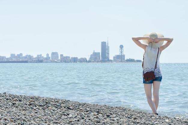 Девушка в шляпе стоять вдоль берега моря. город на расстоянии. вид сзади