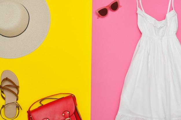 白いサンドレス、赤いハンドバッグ、茶色の靴、サングラス。明るいピンクと黄色の背景