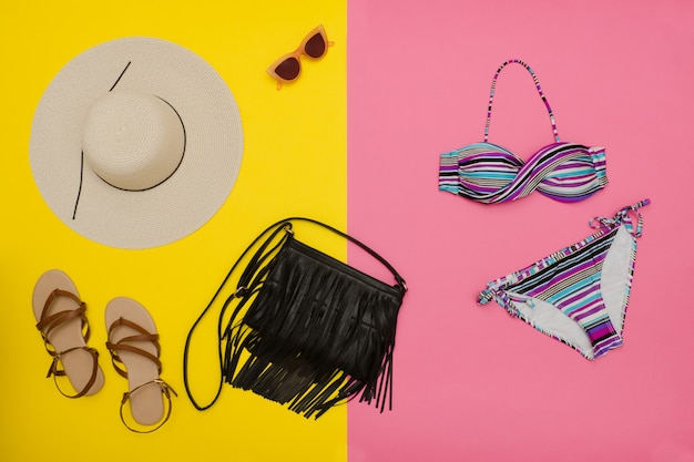ビーチのコンセプト。帽子、サンダル、水着、ハンドバッグ。ピンクの背景、トップビューで黄色
