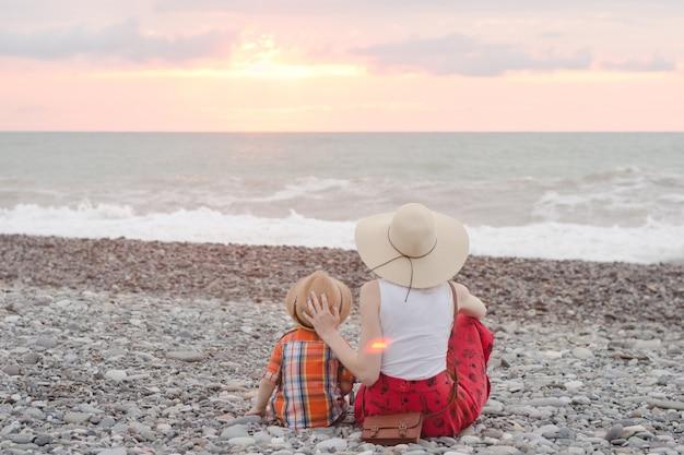 Мама и сын отдыхают на галечном пляже. время заката вид сзади