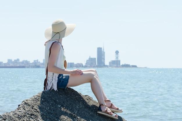 海沿いの岩の上に座っている帽子の少女。遠くの都市。晴れた日