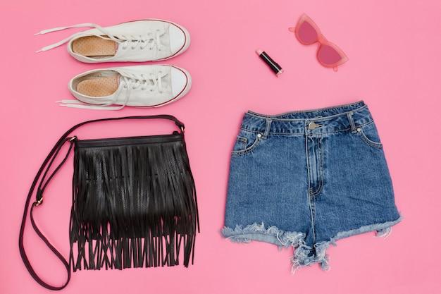 デニムショートパンツ、白いスニーカー、黒いハンドバッグ。明るいピンクの背景。ファッショナブルなコンセプト