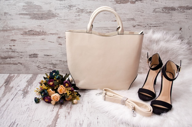 軽いバッグ、黒い靴、白い毛皮の花