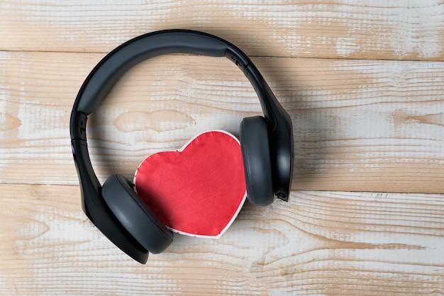 Беспроводные наушники в натуральную величину натянули маленькую красную коробочку в форме сердца на светло-коричневом деревянном столе. люблю музыкальную концепцию. прямо выше