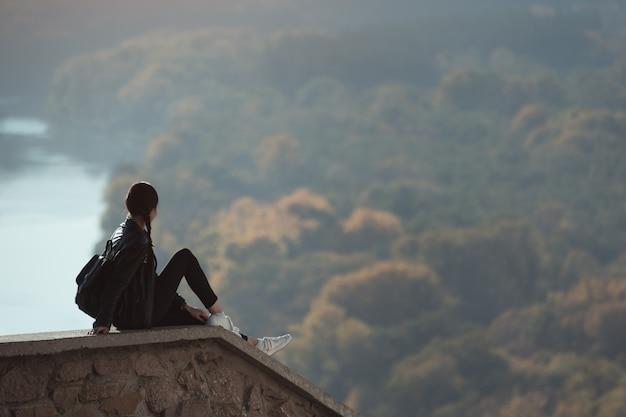 Красивая девушка сидит на холме и смотрит вдаль. наслаждение природой