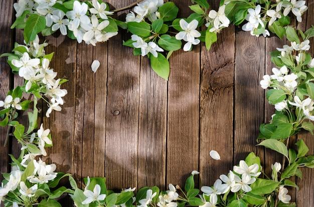 Рамка из яблочных цветов на деревянном полу