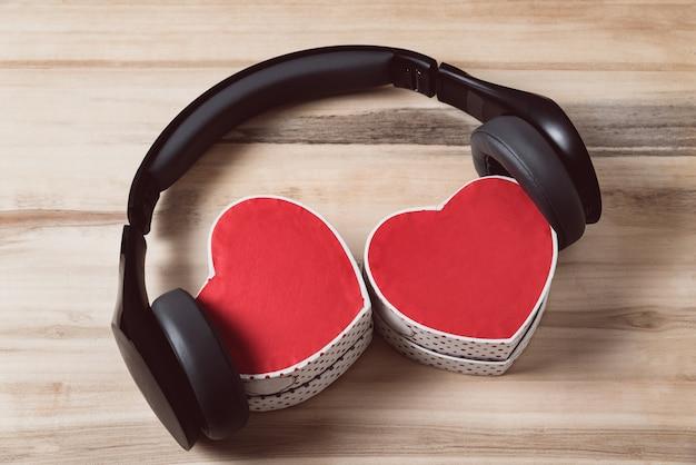 Наушники и две подарочные коробки в форме сердца. музыка сердец. вид сверху