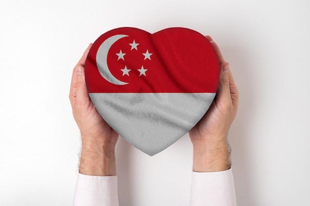 Флаг сингапура на коробке в форме сердца в мужских руках.