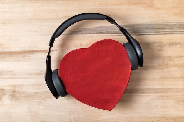 Беспроводные наушники в натуральную величину натянули красную коробку в форме сердца на светло-коричневом деревянном столе. люблю музыкальную концепцию. прямо выше