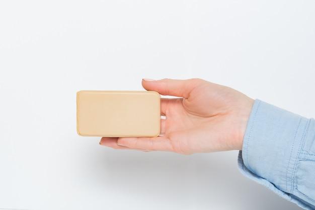 女性の手のひらに石鹸の長方形のバー。分離されました。コピースペース