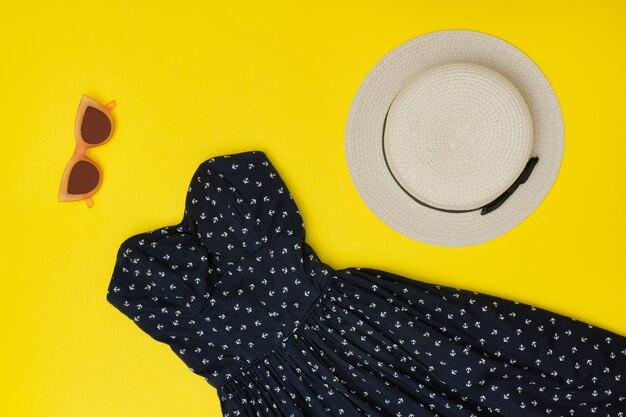 ファッショナブルなコンセプト。女性の夏のワードローブ。麦わら帽子、サンドレス、サングラス。黄色の背景、トップビュー