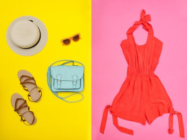 女性のワードローブ。オレンジのオーバーオール、ハンドバッグ、茶色の靴、帽子。ピンクと黄色の背景。ファッションのコンセプト