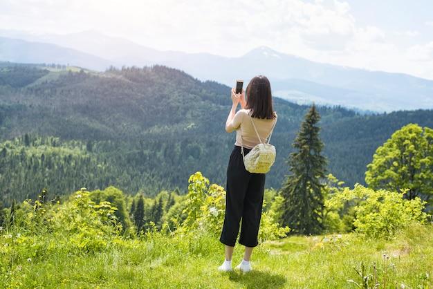 山と森の写真をスマートフォンでバックパックを持つ少女。背面図。晴れた夏の日