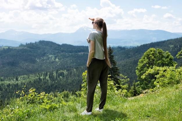 Женщины стоят и смотрят вдаль. лес и горы на заднем плане
