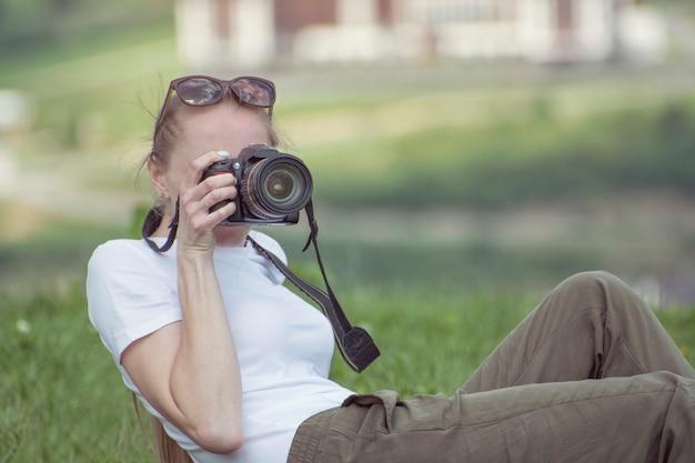 カメラを持つ少女は丘と写真の上に座っています
