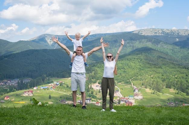 Семейный отдых. родители с маленьким сыном встают с поднятыми руками. горы на заднем плане.
