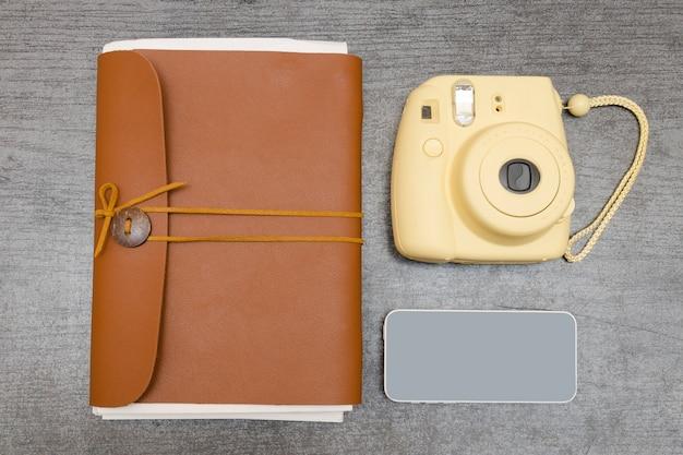 黄色のカメラ、革のノート、黒いテーブルの上のスマートフォン。上面図