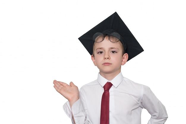 正方形の学術帽子と眼鏡の少年は彼の手のひらを持ち上げます。学校のコンセプト。分離する