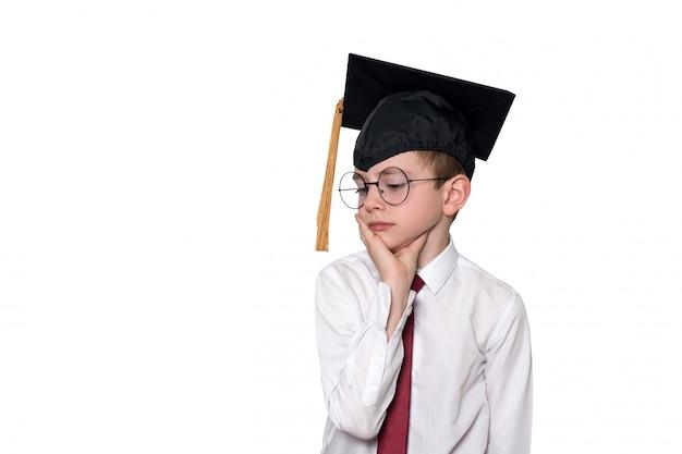 白いシャツ、メガネ、アカデミックキャップで物思いにふける少年の肖像画。学校のコンセプト。分離する