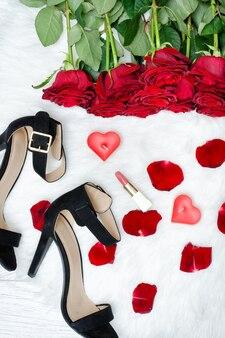 黒い靴と白い毛皮の赤いバラ