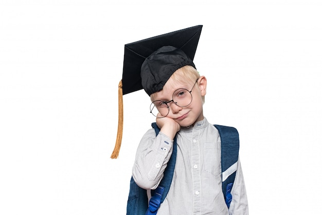 大きなメガネ、アカデミックハット、スクールバッグで物思いにふける金髪の少年の肖像画。白色の背景。分離する