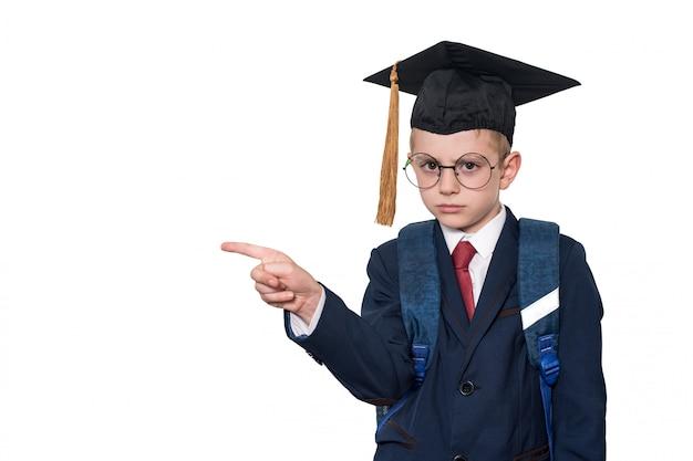 スーツ、眼鏡、アカデミックハットを身に着けている深刻な少年は、指を指しています。学校のコンセプト。分離する