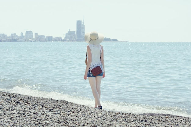 Девушка в шляпе гуляет по берегу моря. город на расстоянии. вид со спины