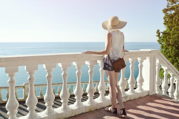 階段の上に立って、海を見て帽子の少女。背面図