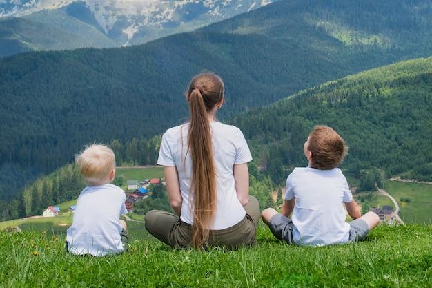 家族の休日。母と二人の息子は山の景色を賞賛します。背面図。晴れた夏の日