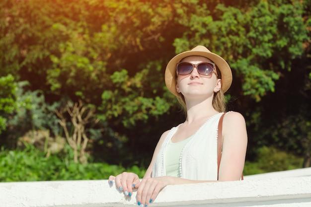 自然を楽しんでいるサングラスと帽子の少女。晴れた日、公園