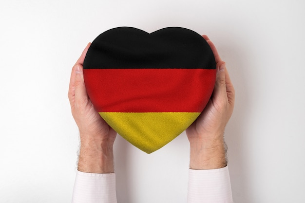 男性の手でハート形のボックスにドイツの旗。