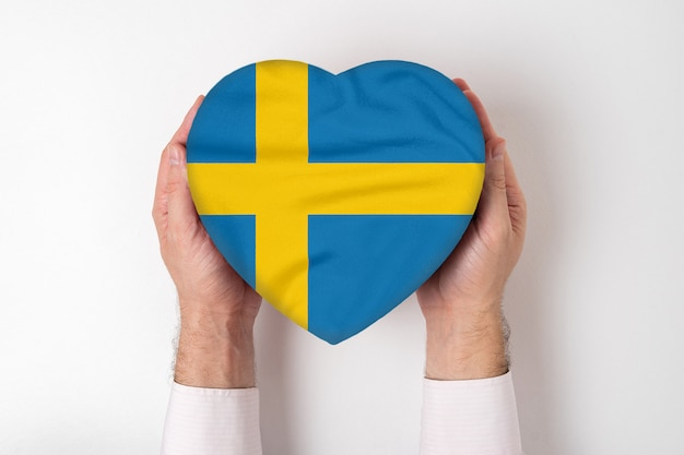 男性の手でハート型のボックスにスウェーデンの旗。