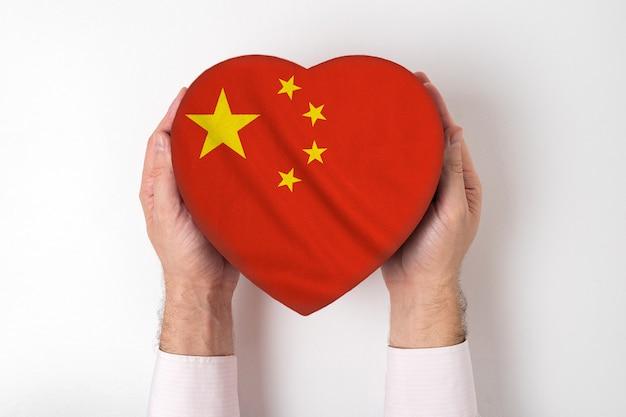男性の手でハート型のボックスに中国の旗。