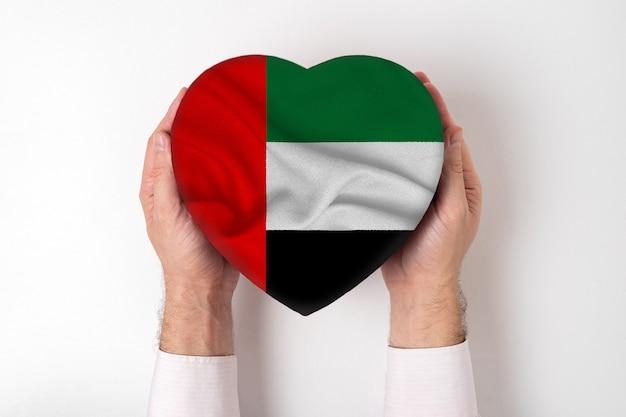 男性の手でハート形ボックスにアラブ首長国連邦の旗。