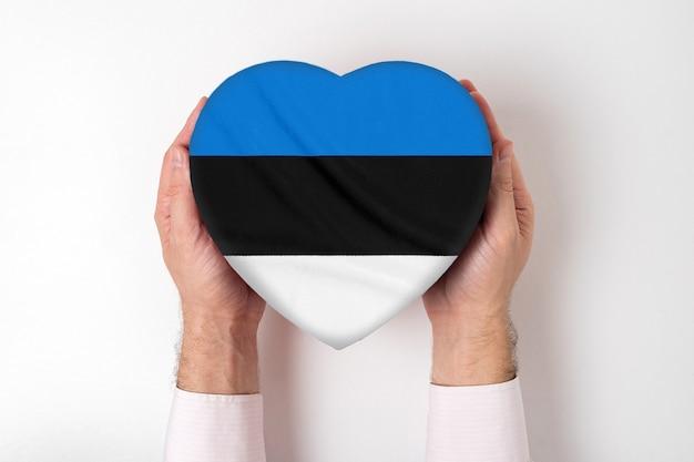 男性の手でハート型ボックスにエストニアの旗。