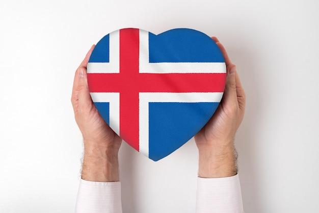 男性の手でハート型のボックスにアイスランドの旗。