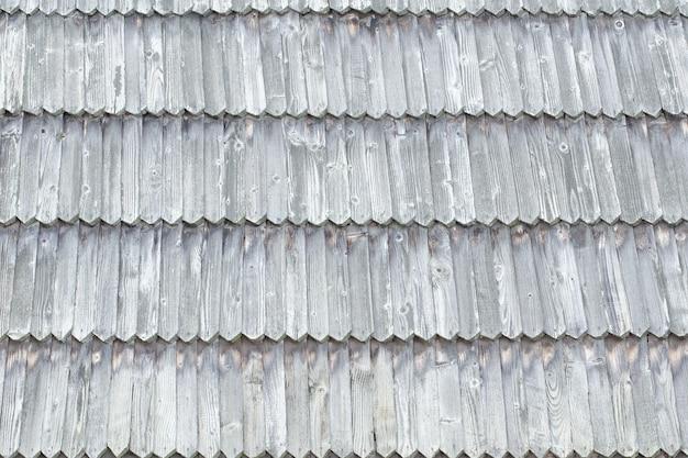古い屋根は木製のタイルでできています。テクスチャ背景。