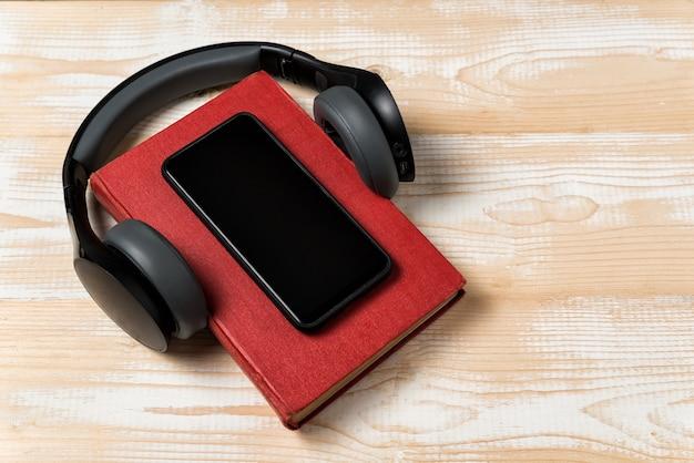 ヘッドフォンで本のスマートフォン。オーディオブックのコンセプト。明るい木製の背景。上面図