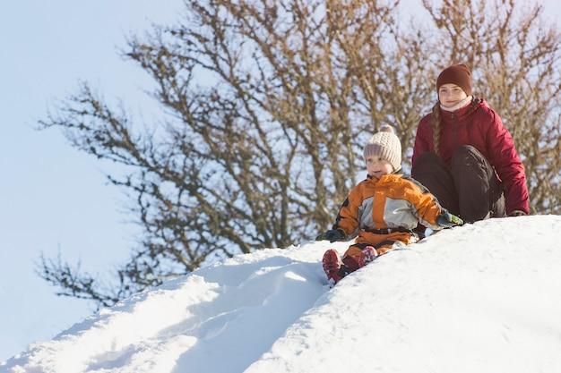 Мама и сын движутся вниз по снежной горке.