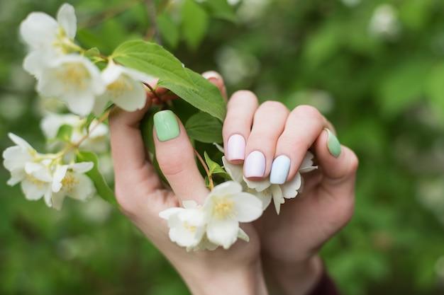 短い爪にきちんとした春のマニキュア。ジェルポリッシュサマーデザイン。手とジャスミンの花。
