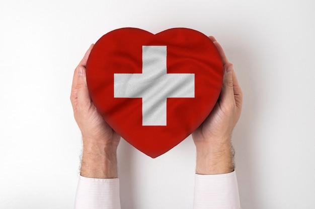 男性の手でハート形のボックスにスイスの旗。