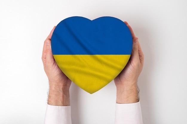 男性の手でハート型ボックスにウクライナの旗。