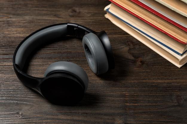 木製の背景の本とイヤホン。音楽を読んで聞いてください。