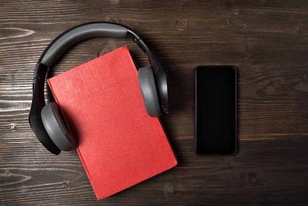 赤い本、ヘッドフォン、木製の背景に携帯電話。オーディオブックの概念。上面図