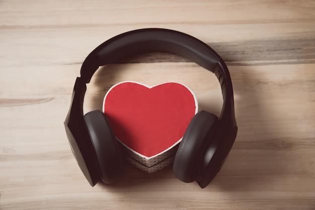 Беспроводные наушники в натуральную величину натянули маленькую красную коробочку в форме сердца на светло-коричневом деревянном столе. люблю музыку концепции