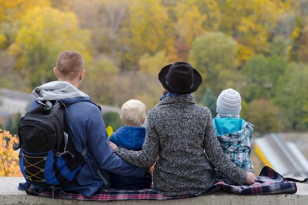 Родители и двое сыновей смотрят на лес высоты.
