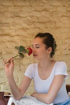 Красивая девушка держит розу и наслаждаться ароматом. свидание в слепую. вертикальная рама