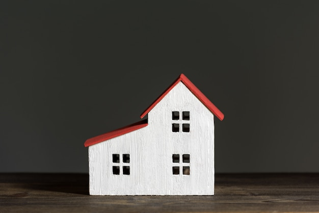 黒い背景にミニチュアの家。家の建設のコンセプト。正面図。