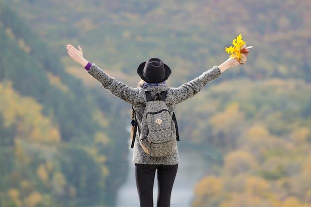 バックパックと丘の上に立っている帽子を持つ少女。