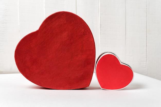 Большие и маленькие красные сердца в форме коробки на столе. вид сбоку. день святого валентина